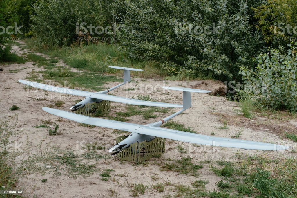 Preparing the army drones for the mission. A pair of reconnaissance aircraft in the wild. stock photo