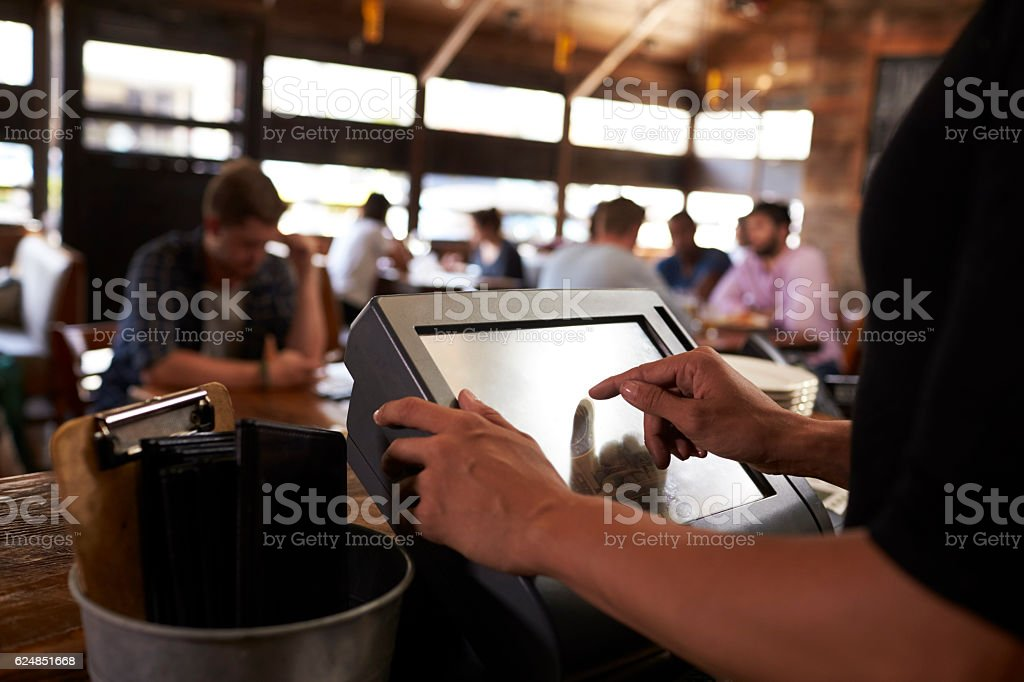 Preparing the bill at a restaurant using a touch screen till stock photo