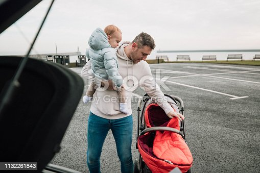Multi-tasking father is in a parking lot, holding his baby boy in one arm while setting up his pushchair with the other.