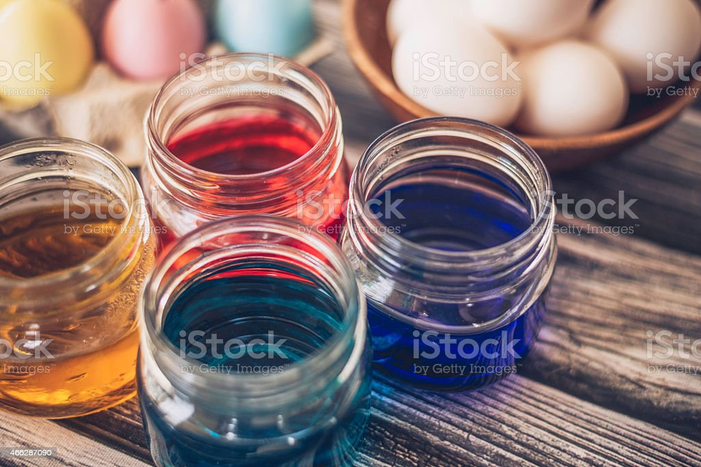 Preparing to dye eggs for Easter. Jars with colored dyes.