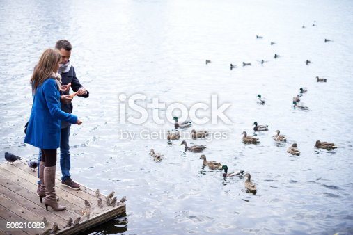 Couple preparing to feed water birds standing on wooden footbridge by the river