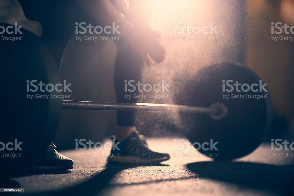 Preparing to lift dumbell in a gym stock photo