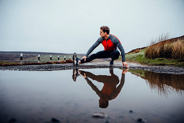 Preparing to run! Male runner training outdoors in wet weather. His reflection seen in a puddle of water before him. He stretched his leg. bending stock pictures, royalty-free photos & images