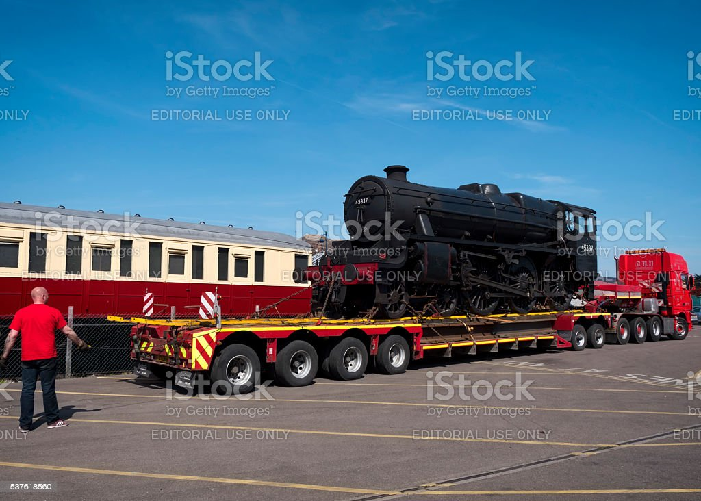 Preparing to unload a steam engine from a lorry stock photo