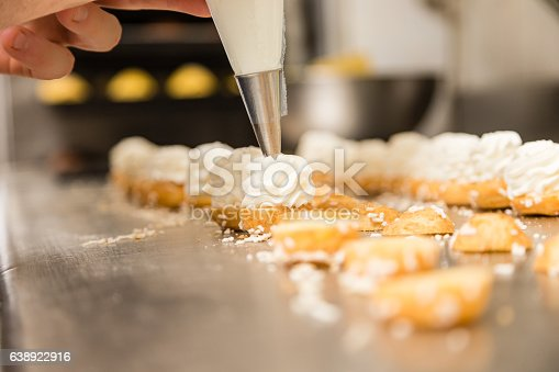 chef prepating cake with a pastry bag