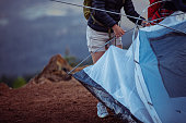 Cropped image of a young woman helping her friends to set up the tent.