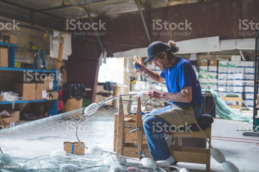 An Alaskan fisherman prepares and checks gill nets in his work space...