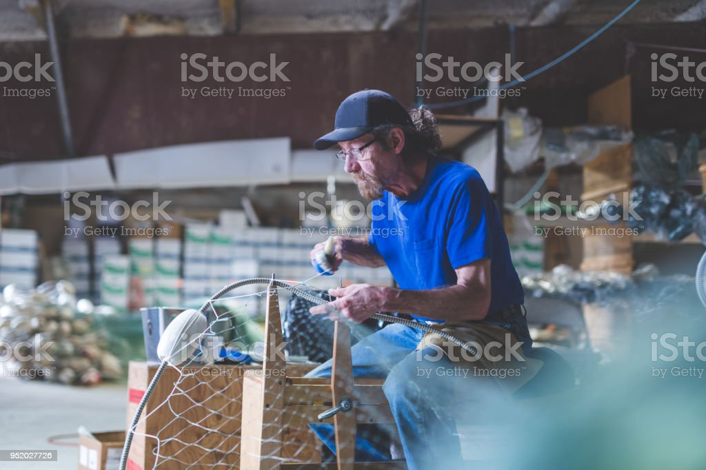 An Alaskan fisherman prepares and checks gill nets in his work space....