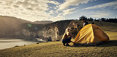 Shot of an affectionate young couple setting up their tent in the mountains
