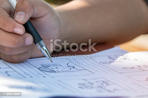 istock Pre-production for film movie story concept : Hands drawing storyboard animation comic carton, design creative scene layout at studio. Behind making work before production films or video shot 1136920885