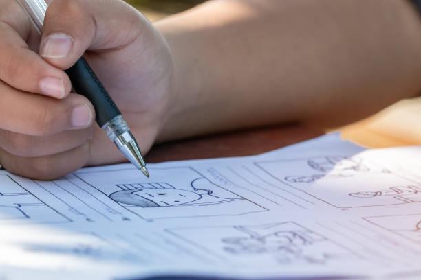 vorproduktion für das film-film-geschichtskonzept: hände zeichnen storyboard-animations-comic-karton, design creative szene layout im studio. hinter der arbeit vor der produktion von filmen oder videoaufnahmen - comic stock-fotos und bilder