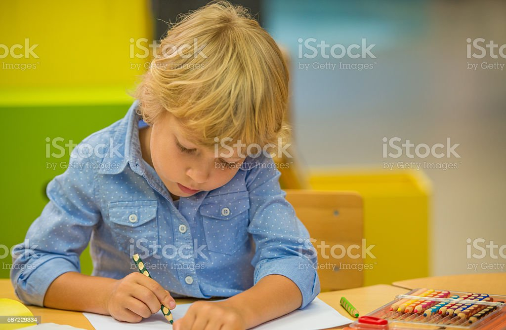 Prescholl Boy Sitting At Table And Draws stock photo