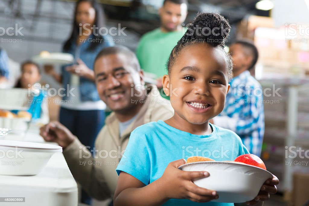 Preschool age African American child at soup kitchen with family stock photo