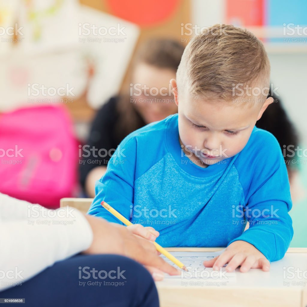 A serious preschool age little boy sits at a table in his classroom...