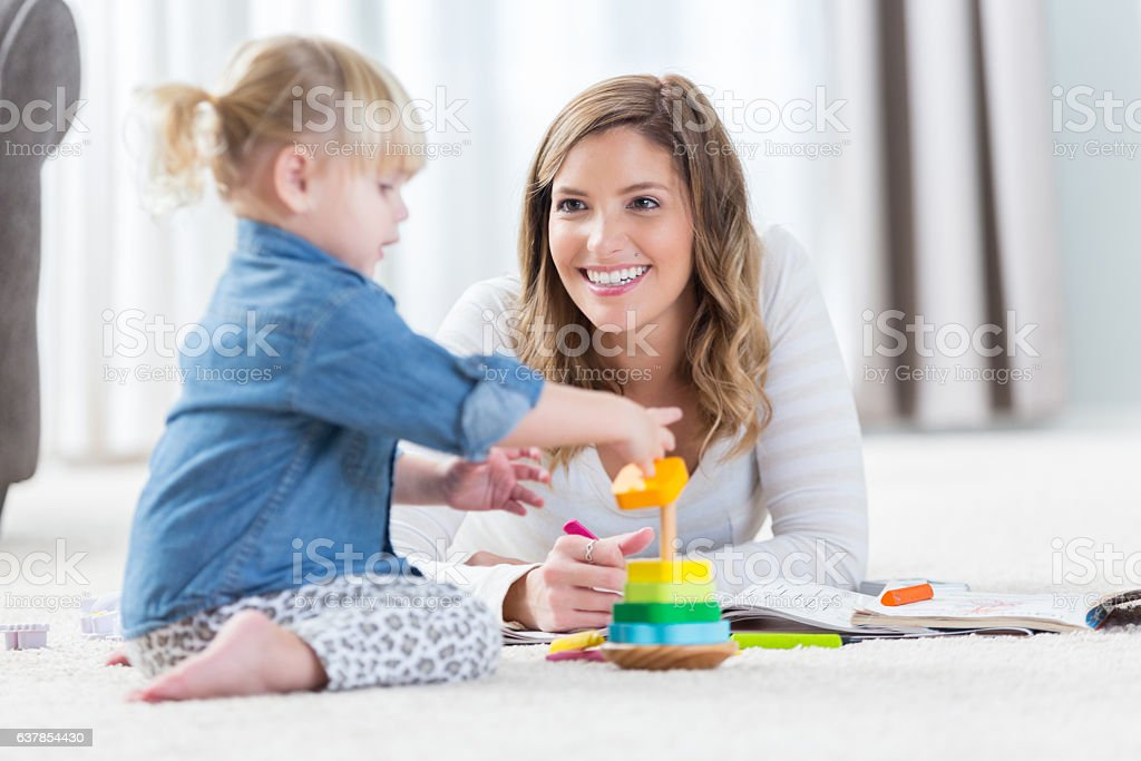 Adorable preschool age girl plays with a stackable toy with her...