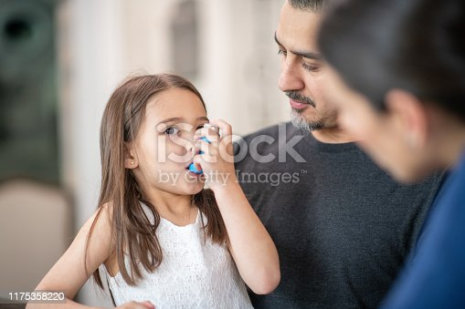 A female doctor is showing a preschool age girl how to use an asthma inhaler.  She is talking her through the process. The young girl is sitting on her dads lap who is also listening attentively.