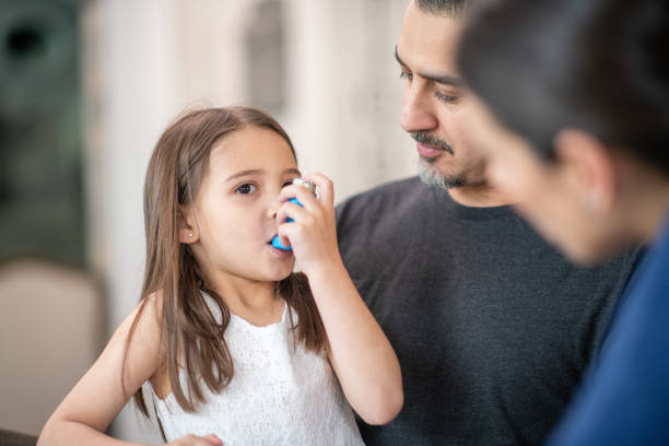Preschool age girl with asthma learns to use an inhaler stock photo