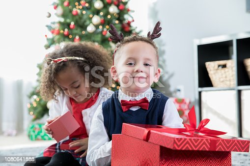 istock Preschool age siblings opening gifts together on Christmas day at home 1080641888