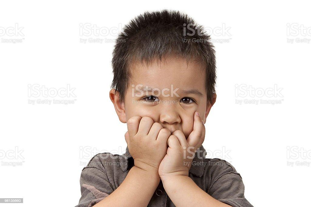 Pre-scolare ragazzo con le mani/i pugni chiusi mettono in bocca foto stock royalty-free