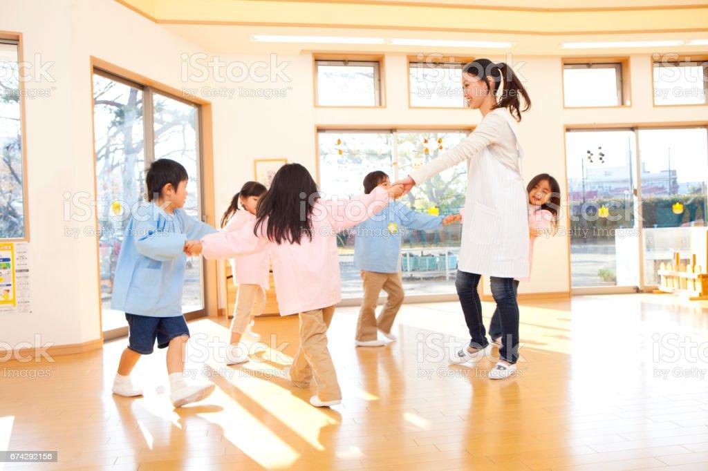 Preschool and kindergarten teachers, dancing in a circle stock photo