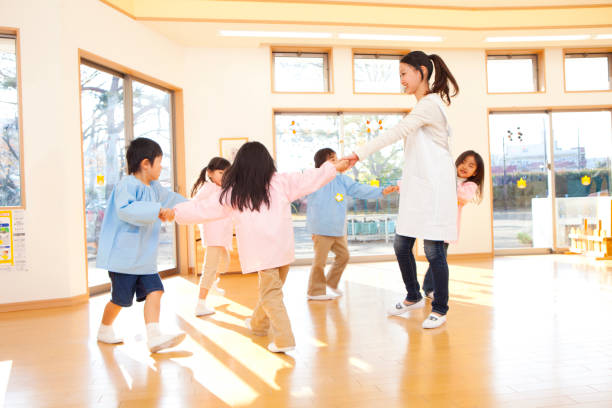 preschool and kindergarten teachers, dancing in a circle - preschool building stock photos and pictures