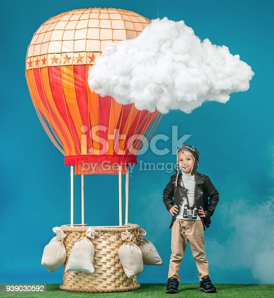 The happy boy dressed as vintage aeronauts clothes standing next to a hot-air balloon