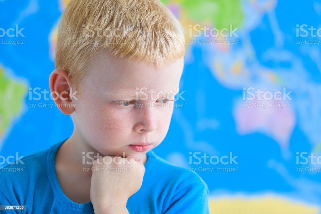 Preschool boy dreaming in front of  world map stock photo