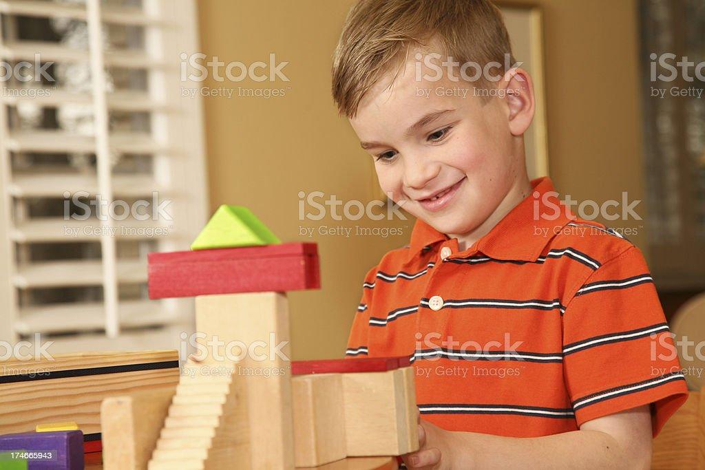 Preschool boy happily working on building blocks royalty-free stock photo