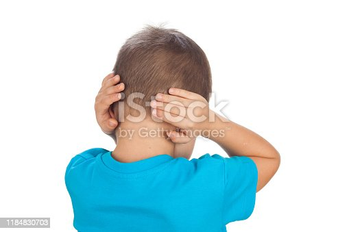 A preschool boy of 5 years and in a blue T-shirt with closed ears, turning to the camera. Isolated on a white background