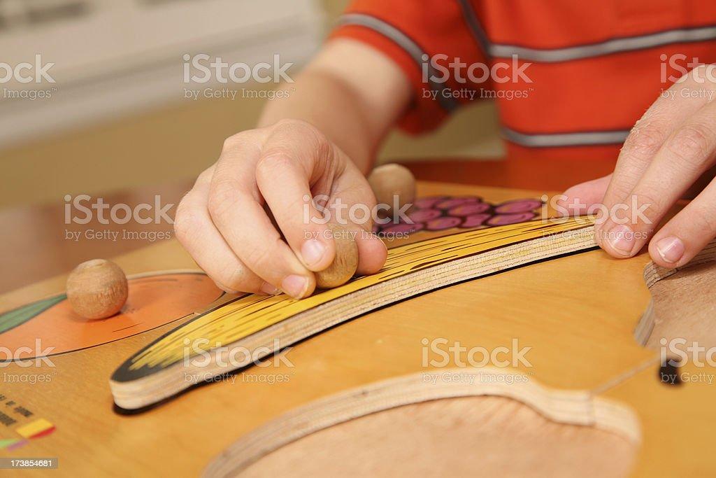 Preschool boy placing a banana piece in wooden fruit toy royalty-free stock photo