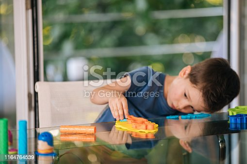 Young boy playing at home with child's play clay