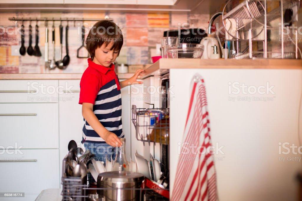 Niño preescolar, niño, ayudando a mamá, poniendo platos sucios en el lavavajillas en el hogar, cocina - foto de stock