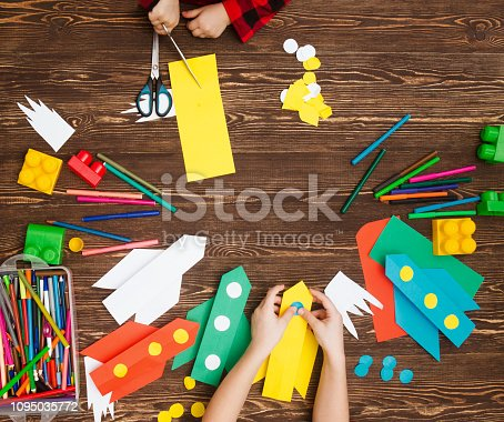 istock preschool Child in creativity in the home. Happy kid makes rockets from paper. Children's creativity. Creative children play with craft. Tools and materials for children's art creativity on table. 1095035772