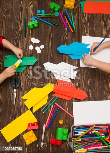 istock preschool Child in creativity in the home. Happy kid makes rockets from paper. Children's creativity. Creative children play with craft. Tools and materials for children's art creativity on table. 1095035780