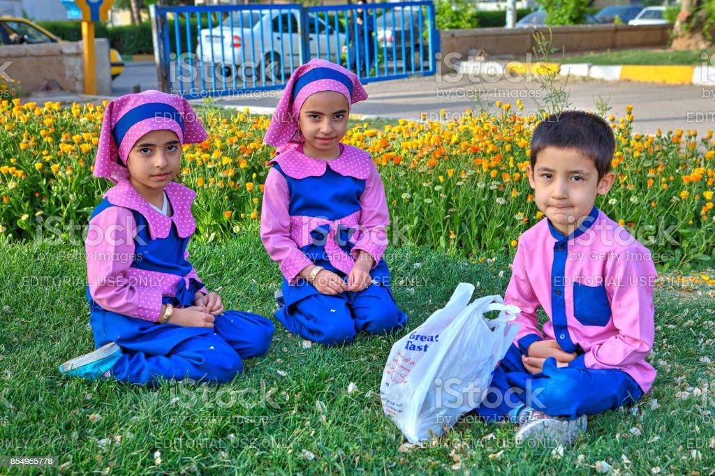 Three preschool children, two girls and one boy dressed in lilac...