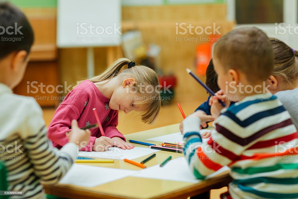 Preschool children drawing and coloring in their classroom stock photo