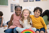 A multi ethnic group of super adorable preschool children smiles and laughs at the camera.