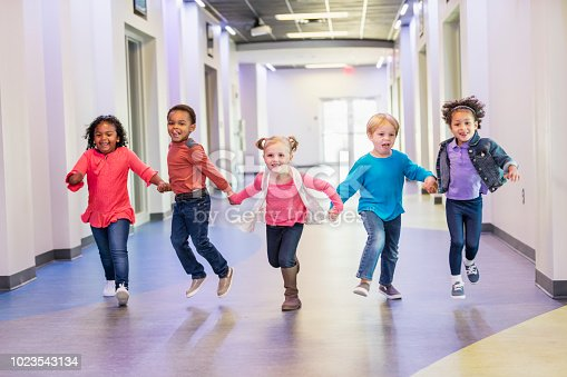 A multi-ethnic group of five preschool children holding hands, running down a hallway in the school building. The boys and girls are all 4 years old.