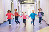 istock Preschool children holding hands running down hallway 1023543134