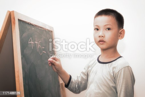161754253istockphoto Preschool children learning in front of the blackboard 1171488125