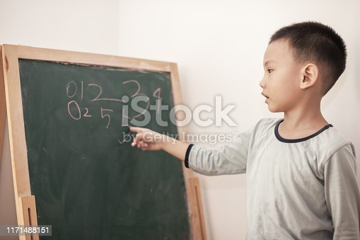 161754253istockphoto Preschool children learning in front of the blackboard 1171488151