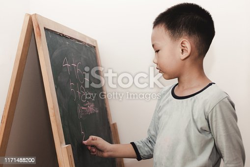 161754253istockphoto Preschool children learning in front of the blackboard 1171488200