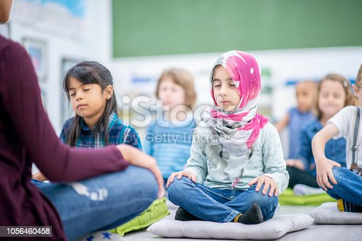 istock Preschool children meditating cross-legged 1056460458