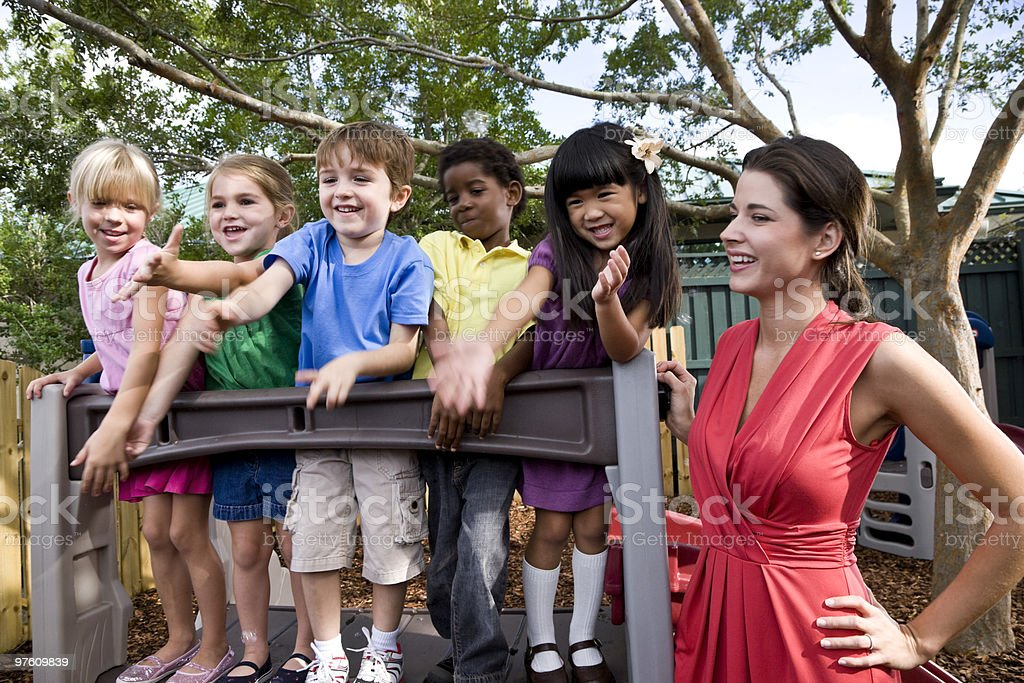 Preschool children playing on playground with teacher royalty-free stock photo