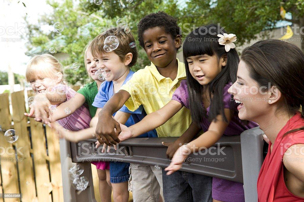 5 preschool children playing on playground with teacher royalty-free stock photo