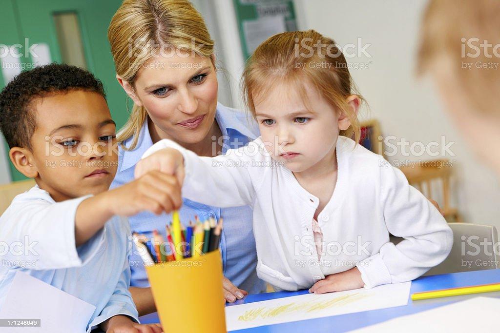 Preschool children with teacher in playroom royalty-free stock photo