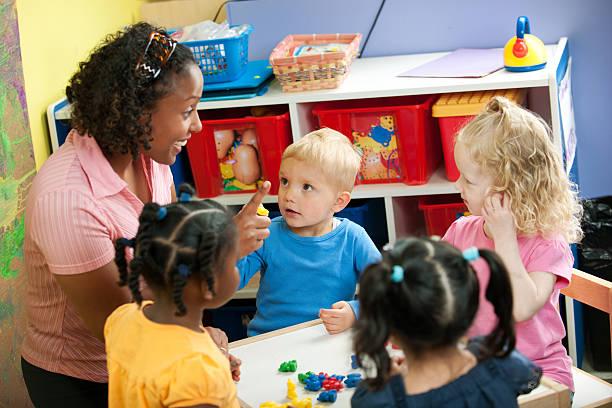 Preschool Daycare Small children at a preschool center. preschool teacher stock pictures, royalty-free photos & images