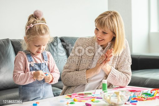 Preschool girl and her mother playing with child's play clay indoors