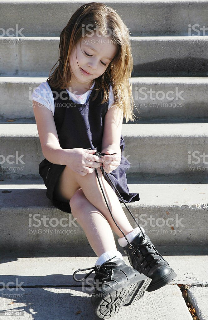 Pre-School Girl in Uniform Tying Shoes royalty-free stock photo