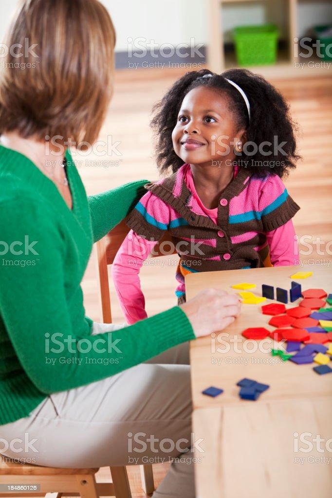 Preschool girl listening to teacher in classroom stock photo